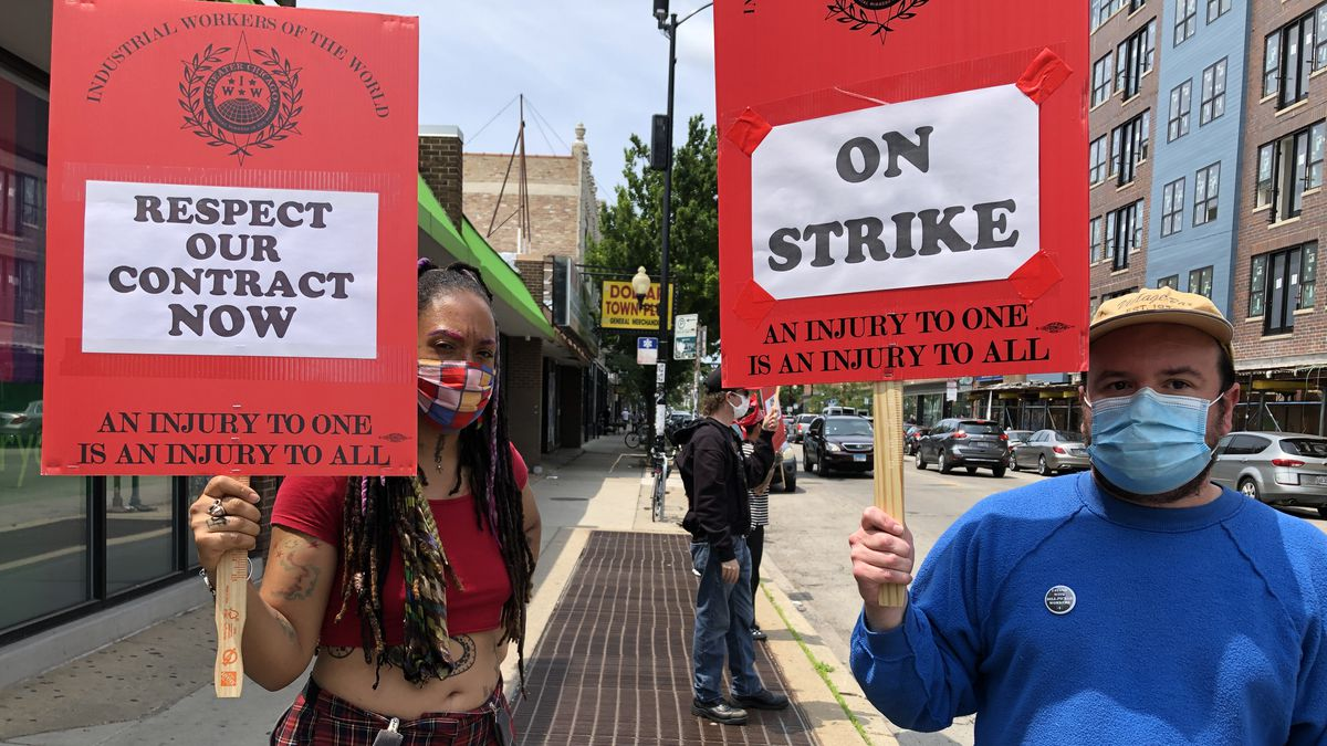 Two masked workers holding picket signs.