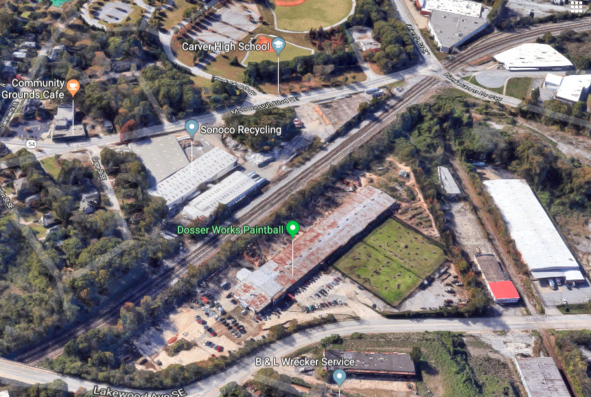 An aerial view of a large green property with rusty industrial buildings around it.
