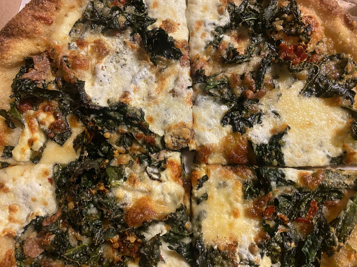 Bits of kale, chile, mozzarella, and anchovy dot the top of a pizza from Smillie Pizza, photographed from above