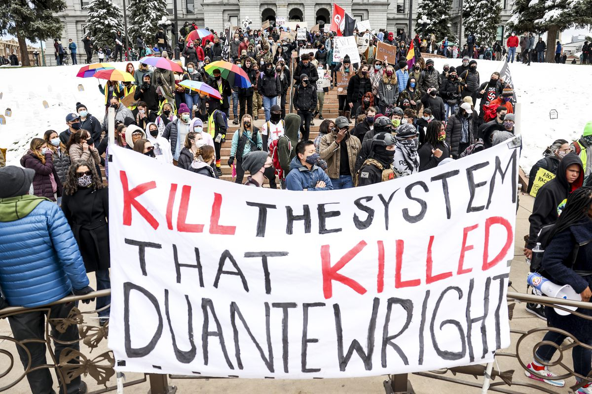 """A mass of protesters in coats gather behind a large white banner that says, """"Kill the system that killed Daunte Wright."""""""
