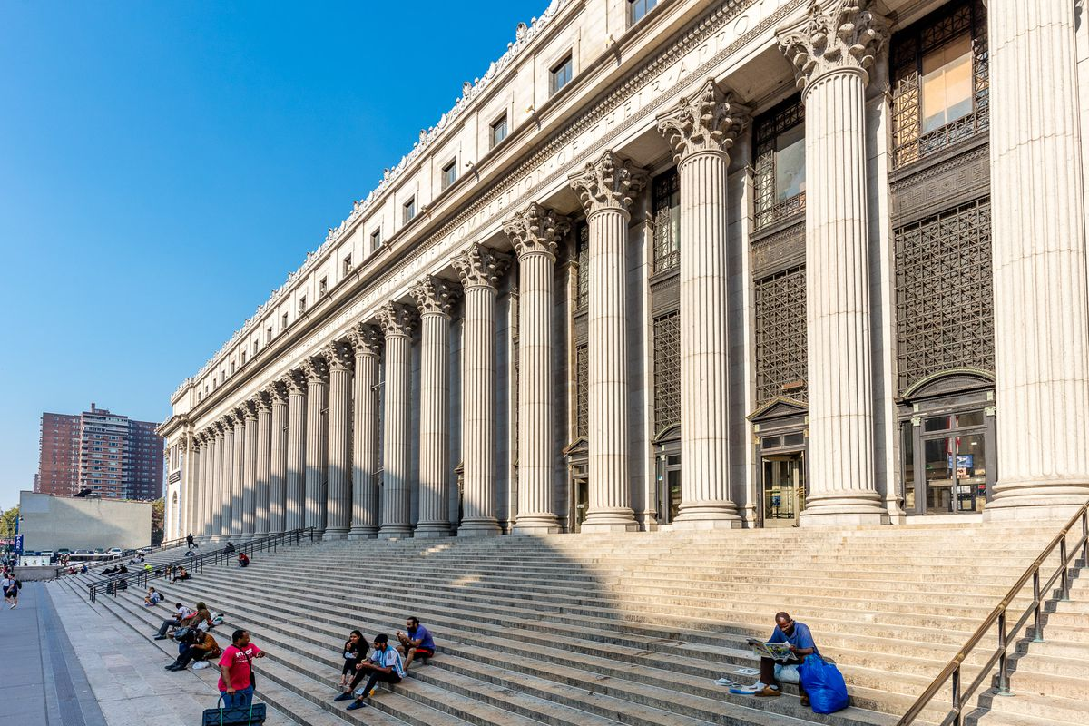 The exterior of a classically designed building with large columns and steps leading to the entrance.