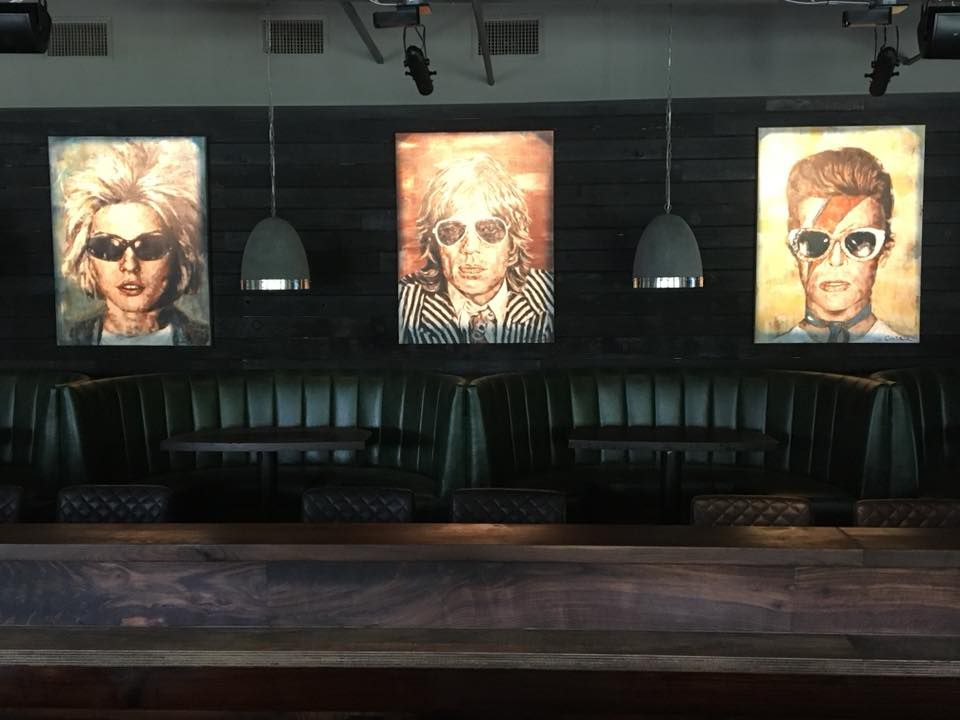 Booth seating with portraits of singers Debbie Harry, Mick Jagger, and David Bowie