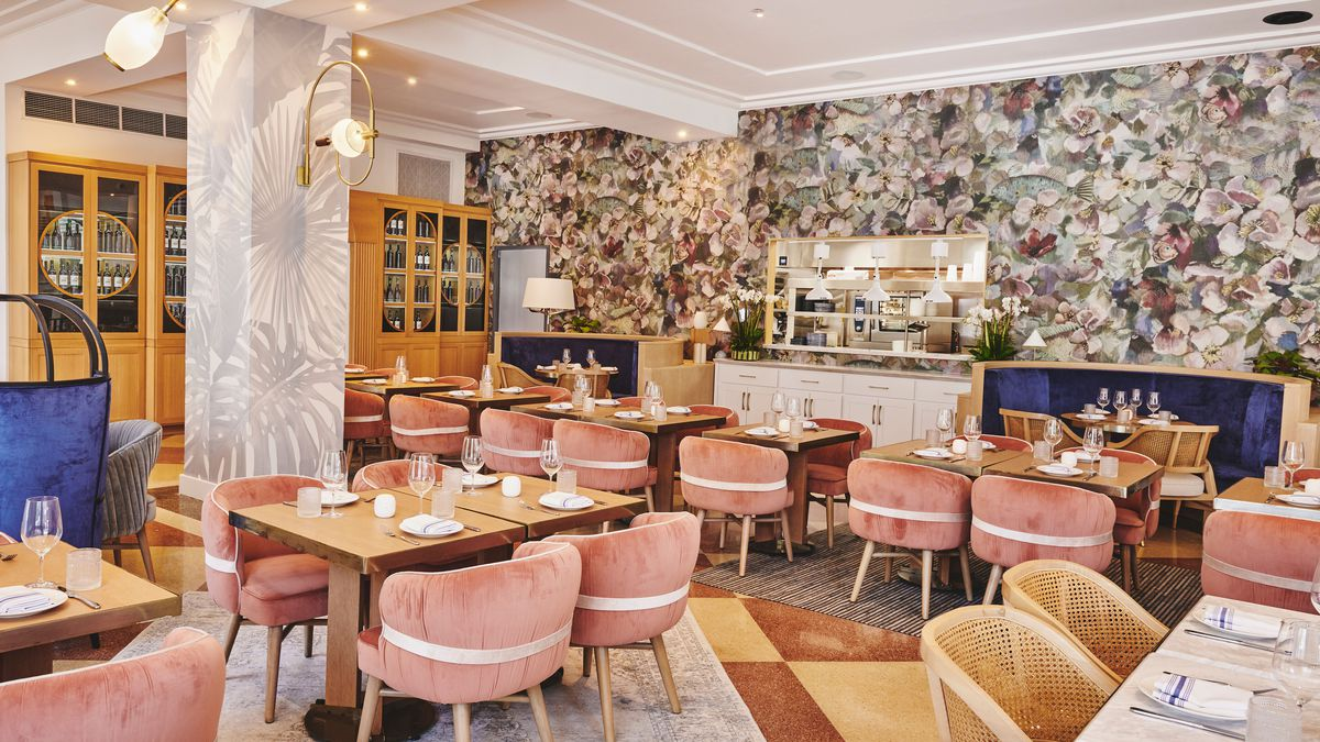 bright dining room with pink dining chairs, wooden tables, Turkish rugs, murals on the wall