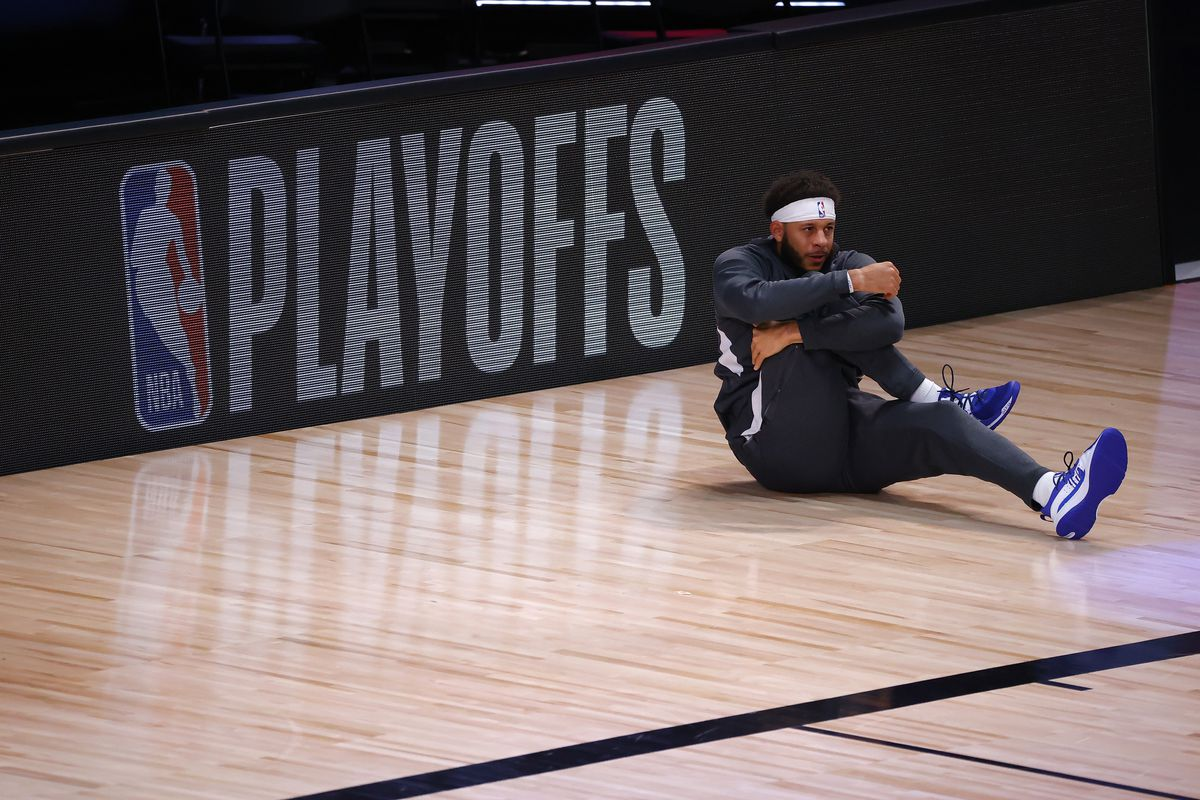 Seth Curry #30 of the Dallas Mavericks stretches in front of the NBA Playoffs logo in Game Six of the Western Conference First Round against the LA Clippers during the 2020 NBA Playoffs at AdventHealth Arena at ESPN Wide World Of Sports Complex on August 30, 2020 in Lake Buena Vista, Florida.
