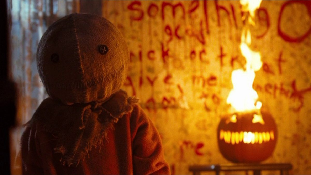 Sam the trick-or-treater standing in front of a burning jack-o-lantern in Trick 'r Treat.
