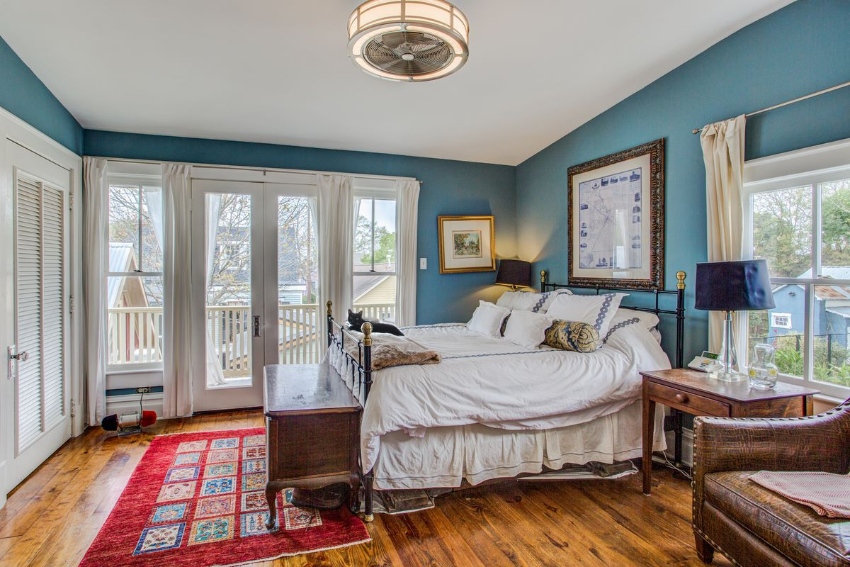 A bedroom with teal walls and a white four poster bed.