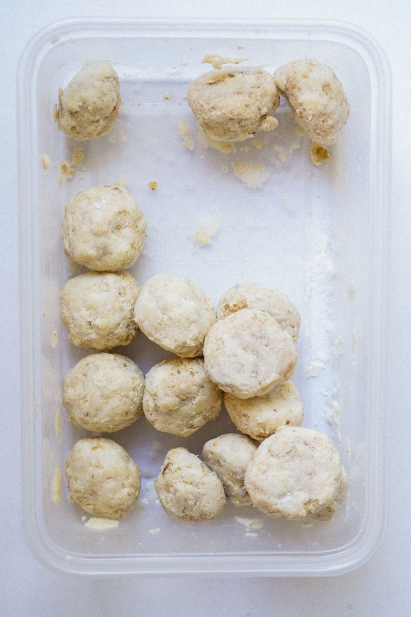 Small round Mexican wedding cookies inside a clear Tupperware.
