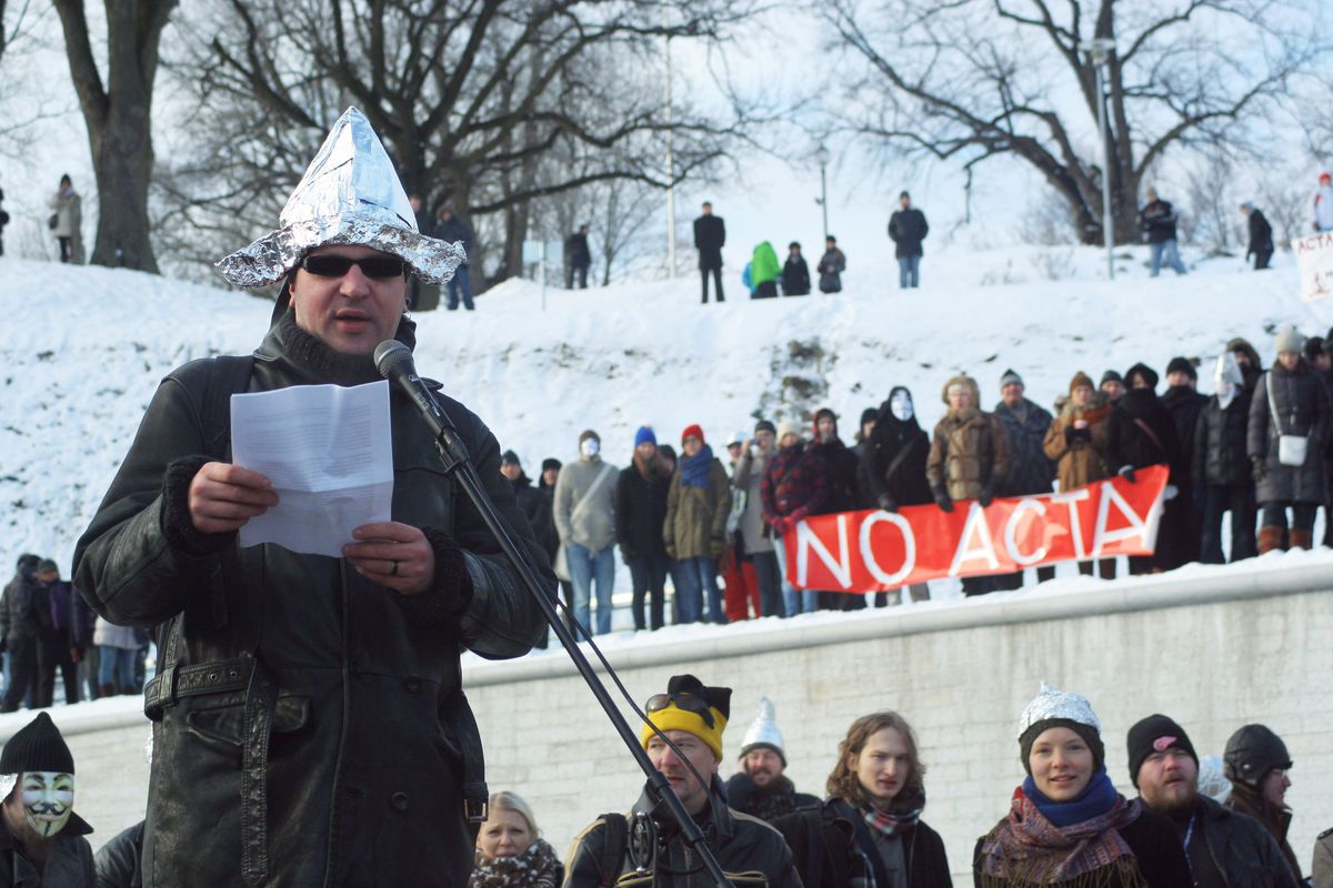 A protester wearing a tinfoil hat delive