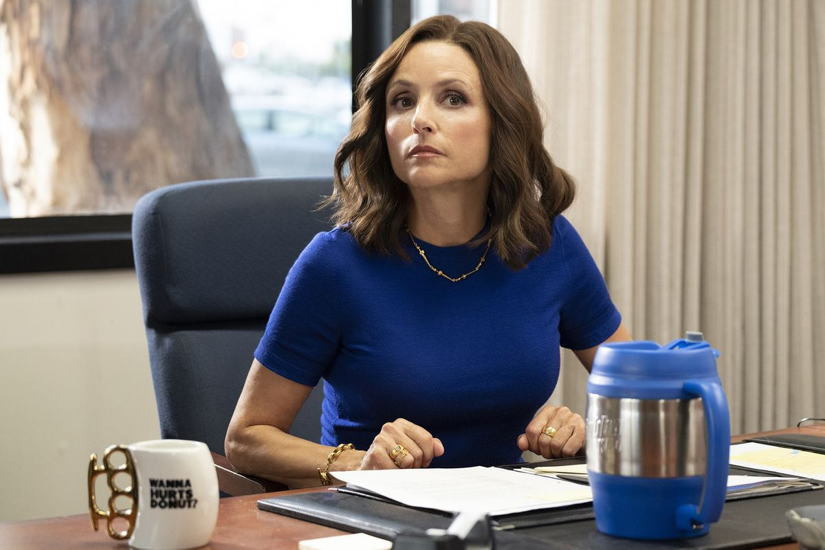 """Selina Meyer, played by Julia Louis-Dreyfus, sitting at a desk on the set of HBO's """"Veep."""""""