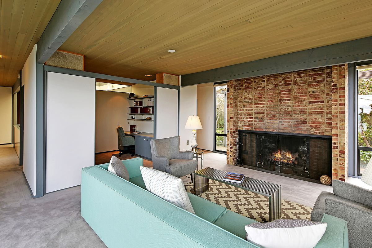 A living area with wood ceilings, gray ceiling beams, and a wide, brick fireplace. A partial wall separates this area from an office off to the side.