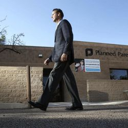 In this photo taken Sunday, Jan. 23, 2011, Bryan Howard, President and CEO of Planned Parenthood Arizona, Inc., walks in front of a Planned Parenthood facility in Tucson, Ariz.  Planned Parenthood, a perennial protest target because of its role in providing abortions, has notified the FBI that at least 12 of its health centers were visited recently by a man purporting to be a sex trafficker but who may instead be part of an attempted ruse to entrap clinic employees.