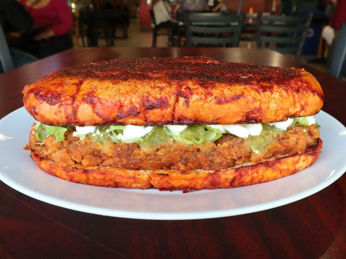 A massive torta, the bread colored by anchiote stuffed with meat, guacamole, and crema