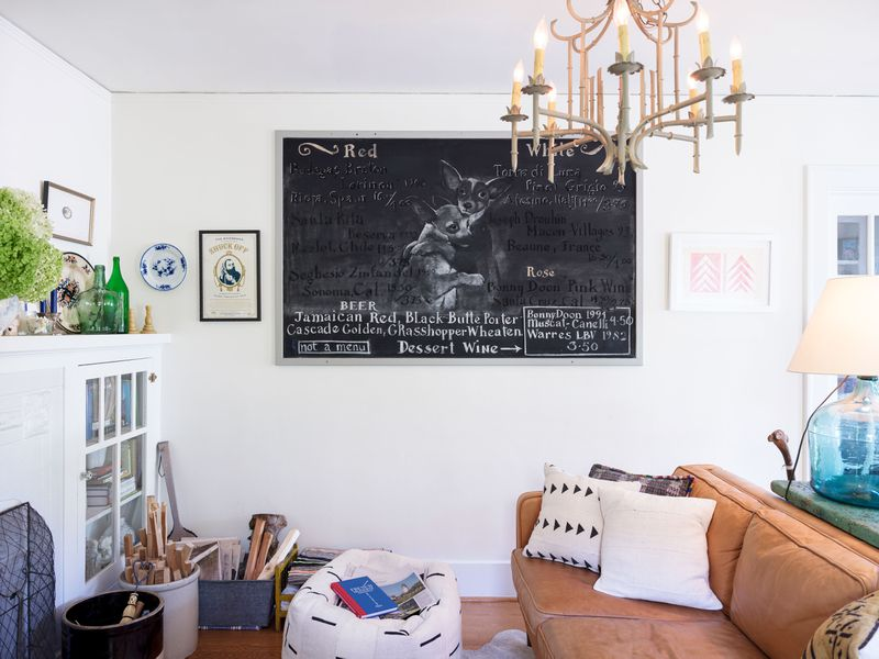 A living area with a couch, table, cabinet, and chandelier. There is a large chalkboard on the wall along with other works of art. A bucket with firewood sits next to the cabinet.
