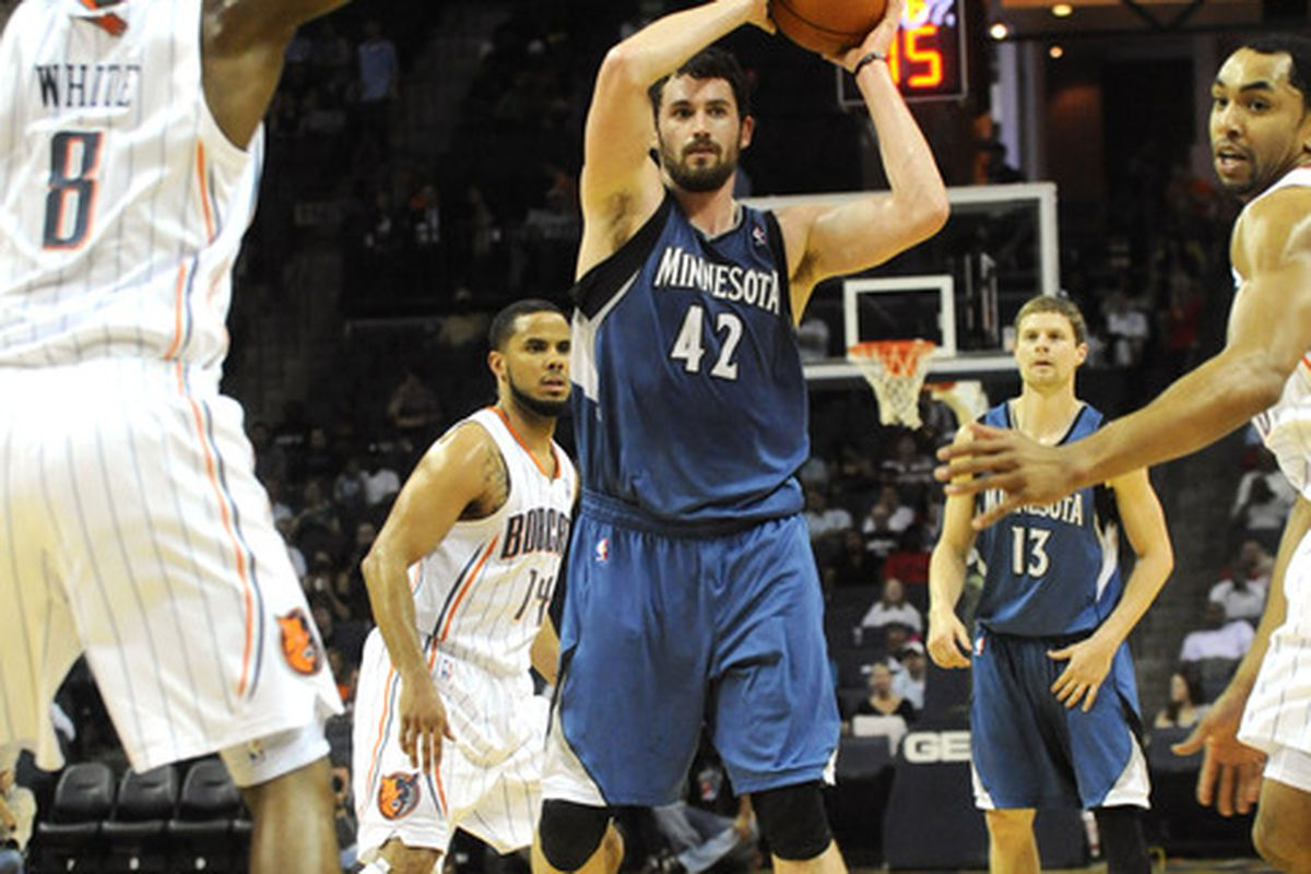 March 28, 2012; Charlotte, NC, USA; Minnesota Timberwolves forward center Kevin Love (42) prepares to pass against Charlotte Bibcats forward D.J. White (8)during the game at Time Warner Cable Arena.  Mandatory Credit: Sam Sharpe-US PRESSWIRE