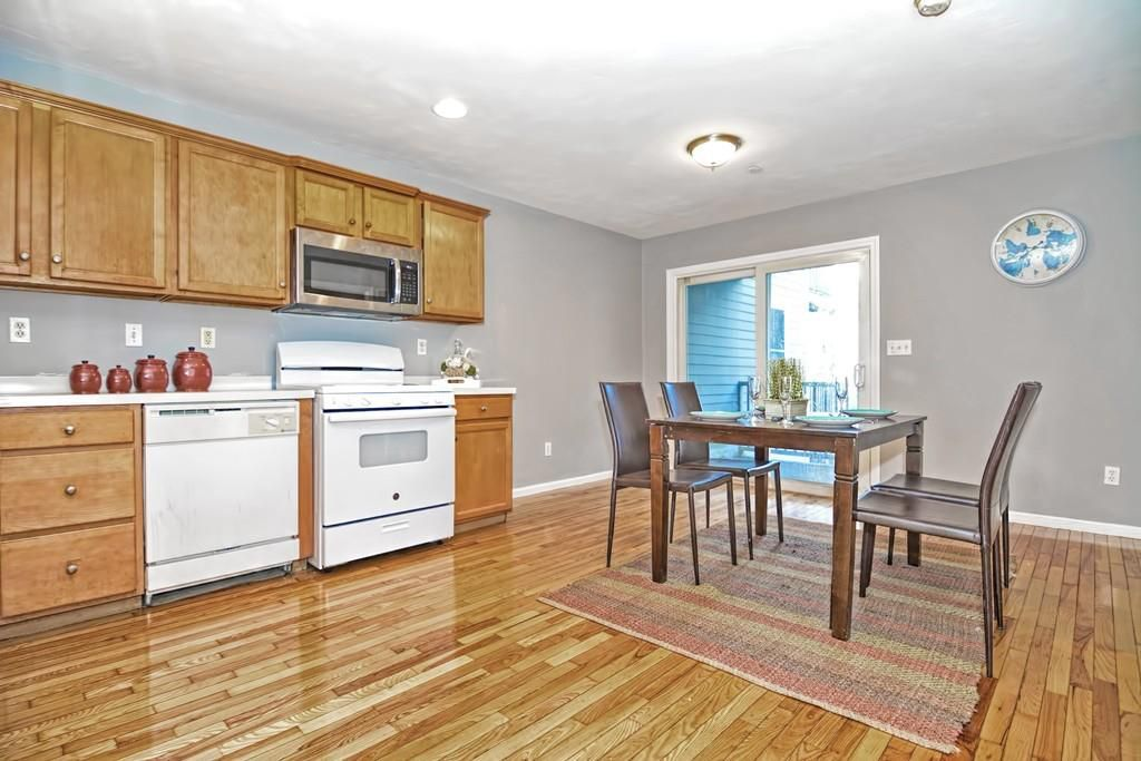 An open and sunny dining room-kitchen area with a table and chairs.