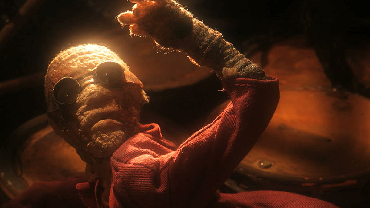 A mummy-like puppet creature in a red coat and sunglasses, about to be hacked up in Phil Tippett's stop-motion movie Mad God