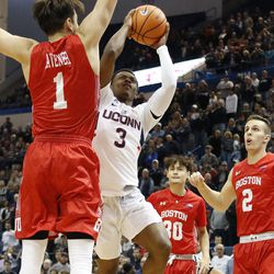 UConn's Alterique Gilbert (3) tries to go around a Boston University defender as he goes for a layup.