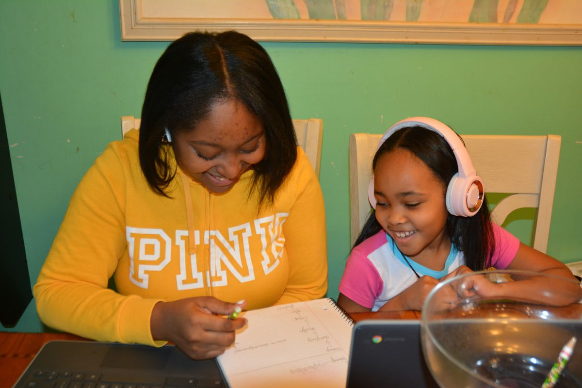 Ramirrah Reid, left, and her younger sister Samya Demercado shown studying together at home.