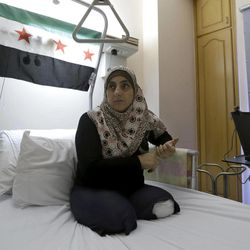 In this Tuesday, Aug. 21, 2012 photo, Hasna Um Abdou, 38, who lost her legs in a Syrian government mortar shelling, which also killed her two children and her husband in March as they fled their home in Homs, Syria by motorcycle, sits on her bed at a hospital in the northern port city of Tripoli, Lebanon. Um Abdou is one of thousands of Syrians who have been wounded in the uprising against Assad and its aftermath. Hundreds of the wounded have been taken for treatment in neighboring countries, mostly to Lebanon, Turkey and Jordan. More than 74,000 Syrians in all have taken refuge in Lebanon, itself a small country of just 3.5 million people that is struggling with instability.