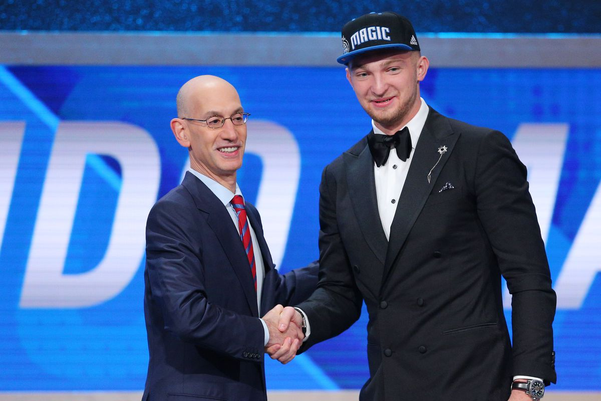 Domantas Sabonis shakes the commissioner's hand after being taken as the 11th pick by the Magic.