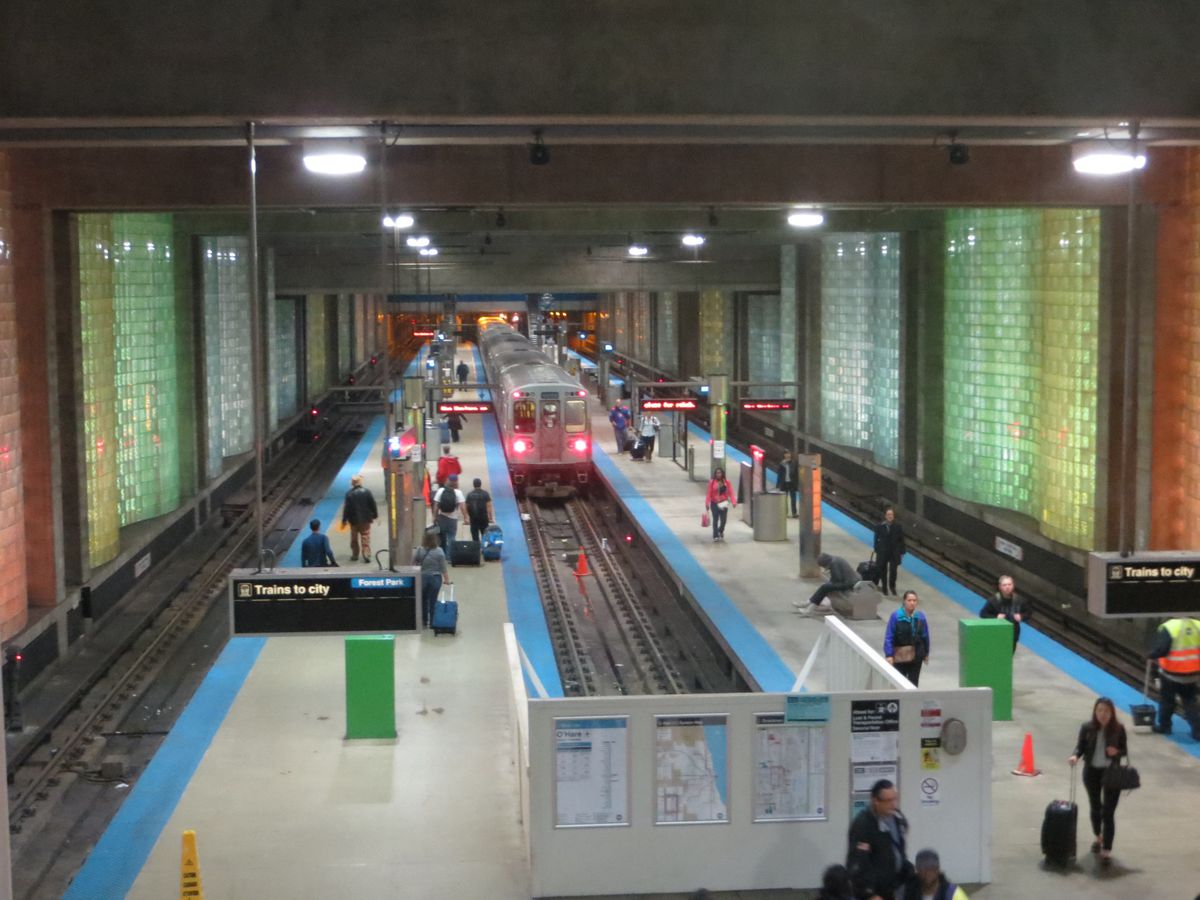 The interior of a three-track, two-platform subway, with a train approaching in the center and people waiting on the platforms. The sides feature blocks of clear glass illuminated by colored lights.
