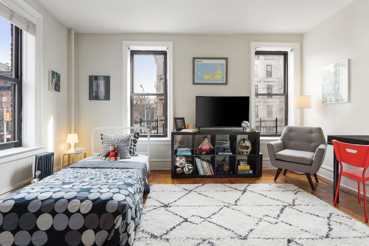 The corner bedroom features three windows overlooking the streets of Park Slope.