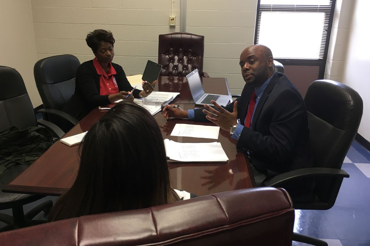 Behavior specialists Clarence Shaw and Inger Spikner speak with a student at Kirby High School in Memphis.