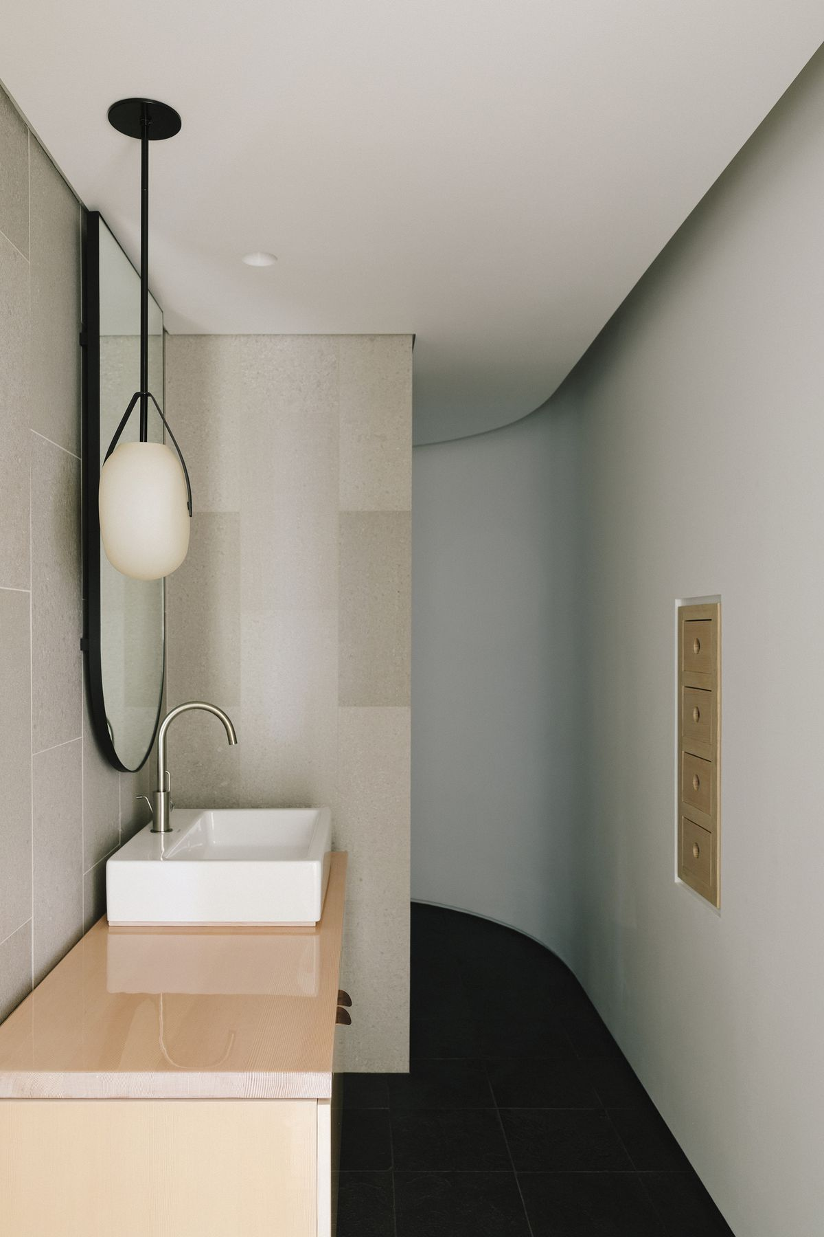 A bathroom. The walls are painted white. There is a sink. The cabinetry is wooden. There is a mirror over the sink and a hanging black and white light fixture.