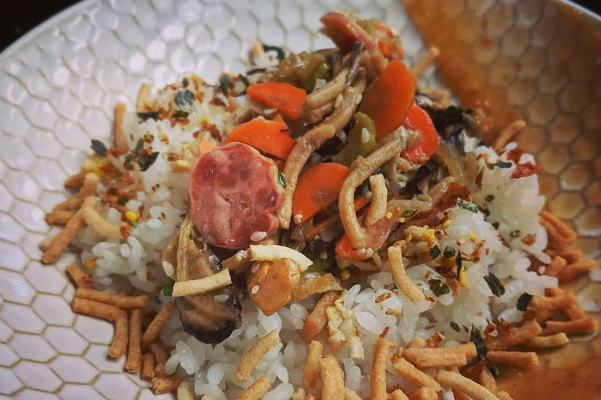 A dish with rice, crispy noodles, chicken, Chinese sausage, and puree