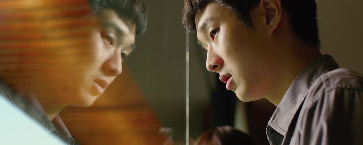 Parasite star Choi Woo-sik presses his head up against a window showing his reflection, looking weary and lost.