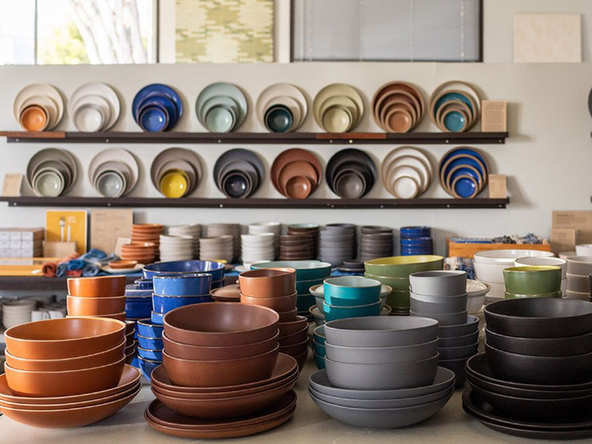 A selection of colorful ceramic bowls and plates and cups all stacked up.