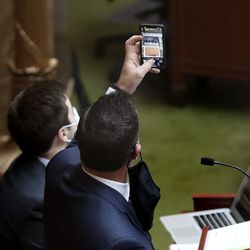 House Speaker Brad Wilson, R-Kaysville, takes a photo of Utah public health directors and workers standing in the House gallery as they are applauded by members of the House of Representatives at the Capitol in Salt Lake City on Wednesday, Feb. 3, 2021. Legislators were voting on HCR6, which recognizes and thanks the individuals who provide accurate data and information to the Legislature, the governor, and Utah citizens in relation to the spread of COVID-19.