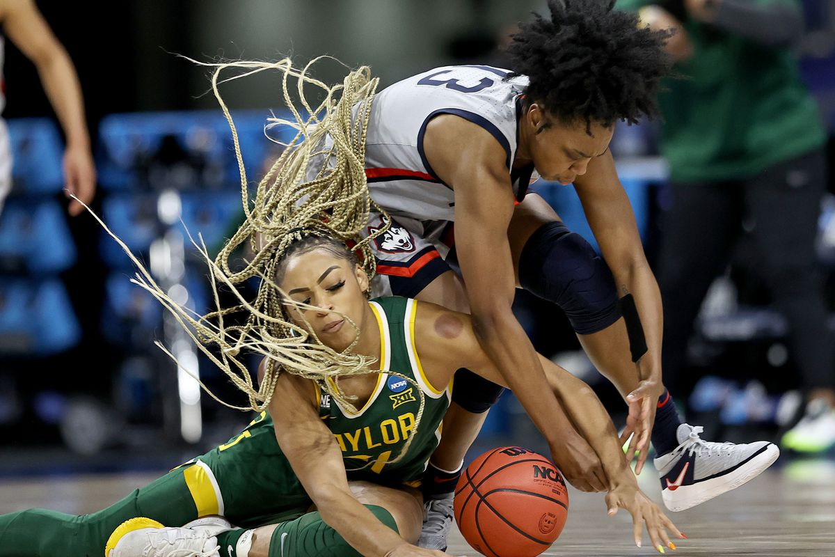 DiJonai Carrington of the Baylor Lady Bears and Christyn Williams of the UConn Huskies go after the loose ball in the first half during the Elite Eight round of the NCAA Women's Basketball Tournament at the Alamodome on March 29, 2021 in San Antonio, Texas.