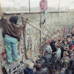 Demonstrators on the west side of the Berlin Wall try to tear down a segment of the wall near the Brandenburg Gate in Berlin, Nov. 11, 1989. East German border guards use hoses to disperse the demonstrators.