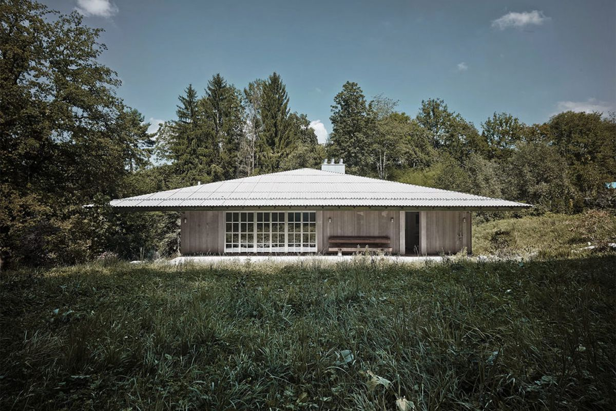 Simple prefab timber home with corrugated metal roof and latticed windows amid nature.