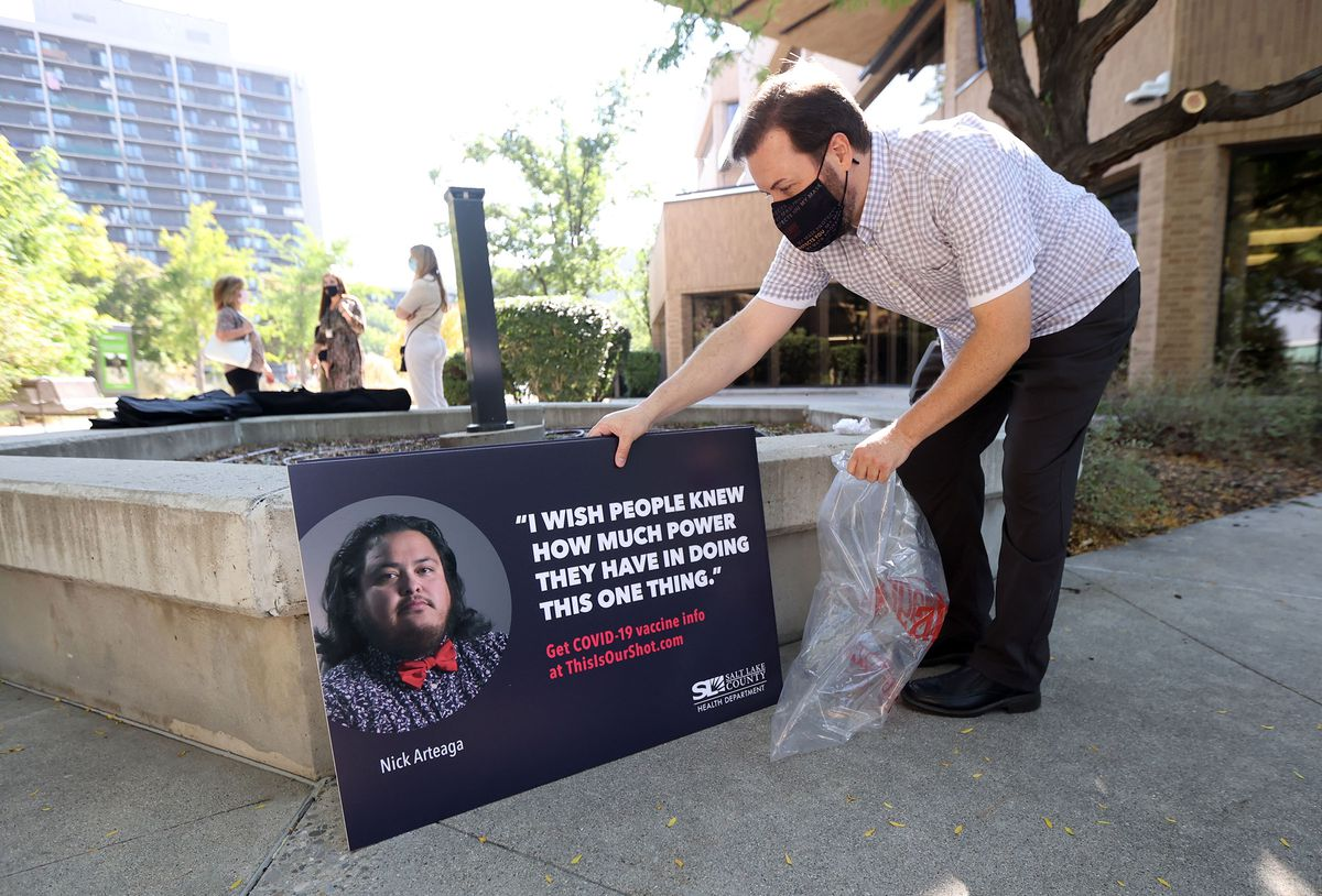 Nicholas Rupp, Salt Lake County Health Department communications and public relations manager, picks up posters for the county's new campaign to help encourage COVID-19 vaccination after a press conference at the Salt Lake County Government Center in Salt Lake City on Tuesday, Sept. 14, 2021. The campaign shares the stories of people from all walks of life who have been deeply impacted by COVID-19.