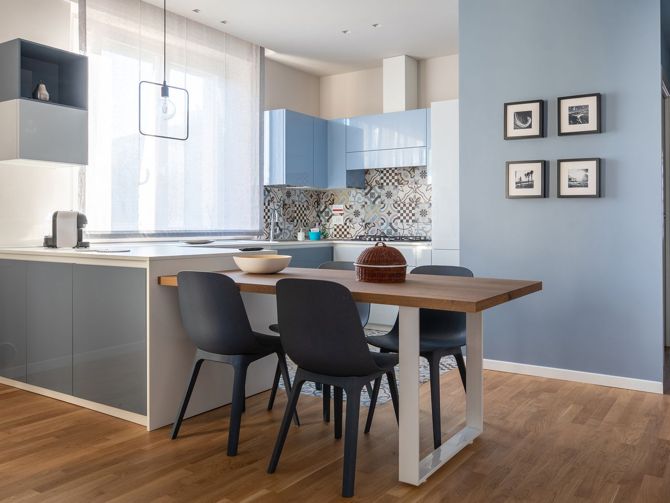 Blue painted kitchen and dining area in a condo.