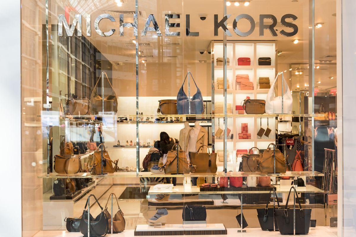 Window showcasing handbags at a Michael Kors store