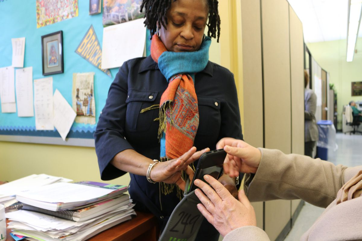 BASE Principal Gail Lambert demonstrates cell phone pouches that the school ultimately abandoned.