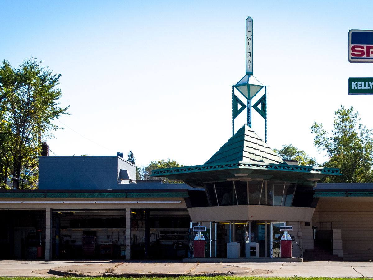 R. W. Lindholm Service Station by Frank Lloyd Wright.  The roof is green and there is a steeple with a sign that reads: F.L. Wright. There are gas pumps in front of the building.