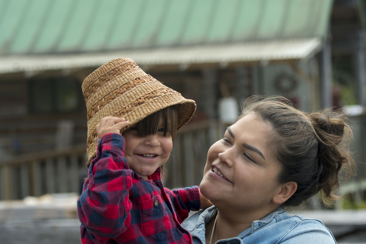 Portrait of a Tlingit mother with her small boy wearing a woven hat.