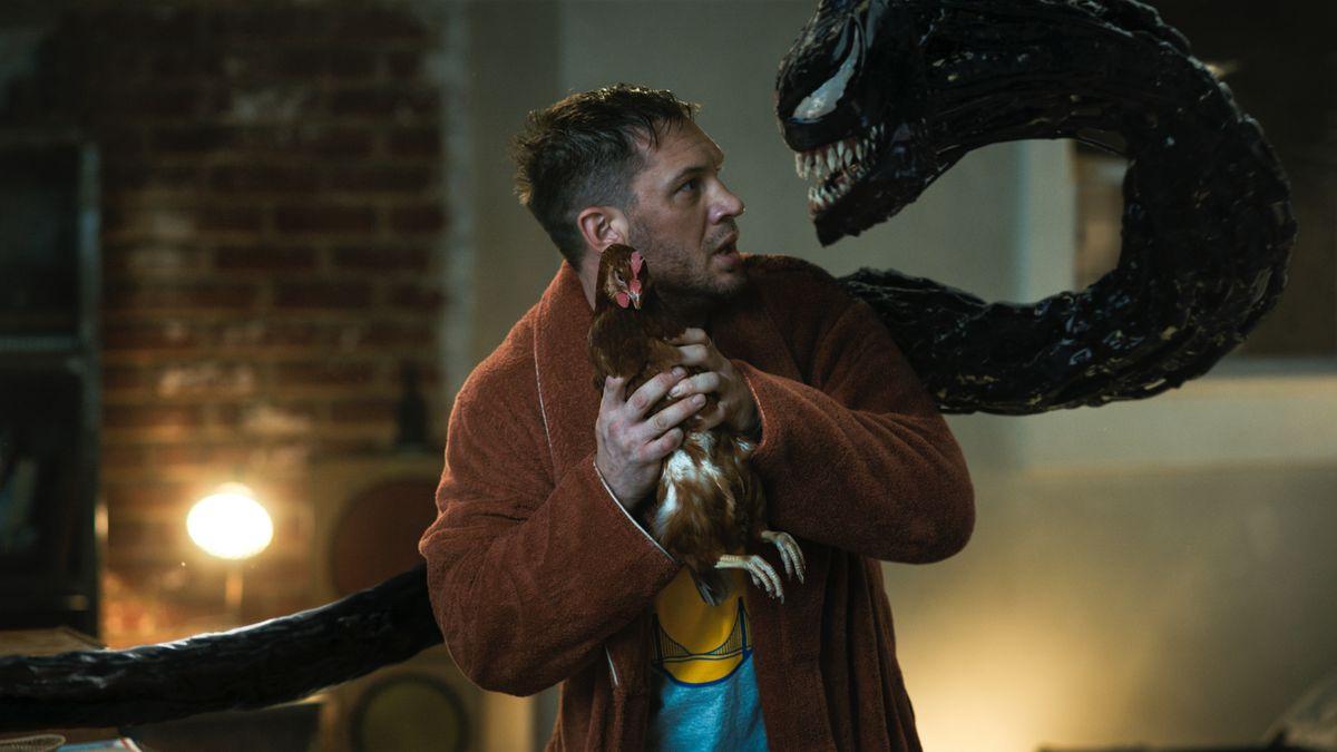 Der Charakter von Eddie hält ein lebendes Huhn, während Venom sich umdreht, um sich ihm zu stellen.