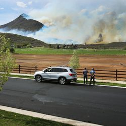 Two people watch as a wildfire burns in the Dutch Hollow area of Midway on Tuesday, May 12, 2020.