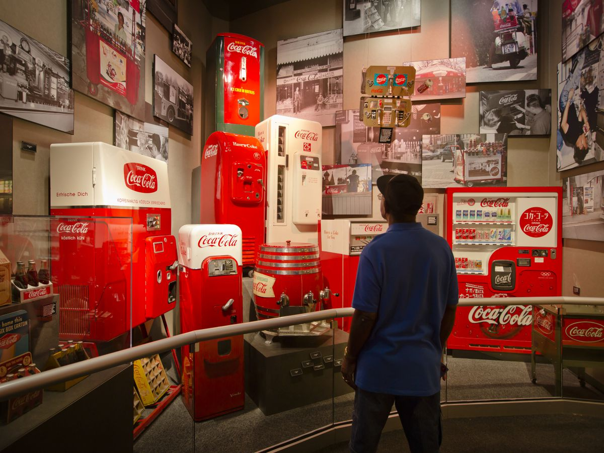 A person stands and looks at a multitude of assorted Coca Cola merchandise and memorabilia.
