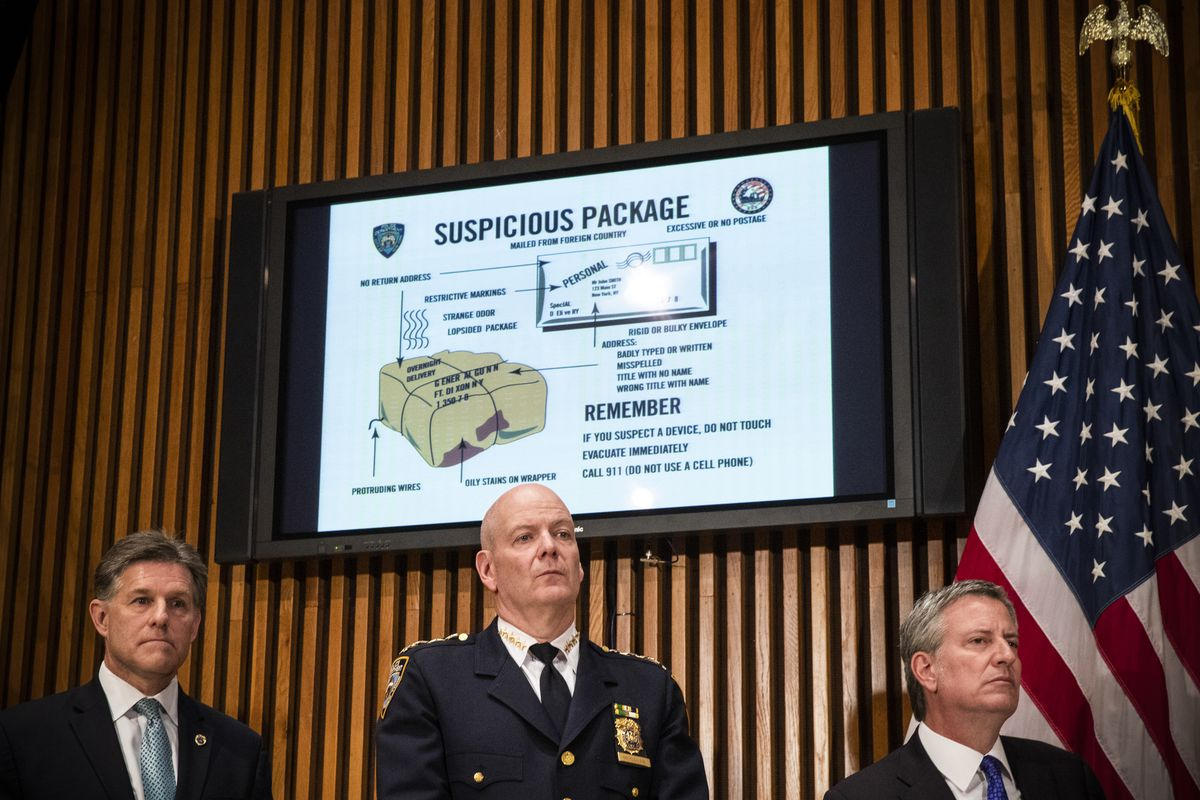A monitor displays information about suspicious packages as NYPD Chief of Department Terence Monahan (center) and New York City Mayor Bill de Blasio (right) hold a press conference regarding the recent package bombings, at NYPD headquarters, in New York C