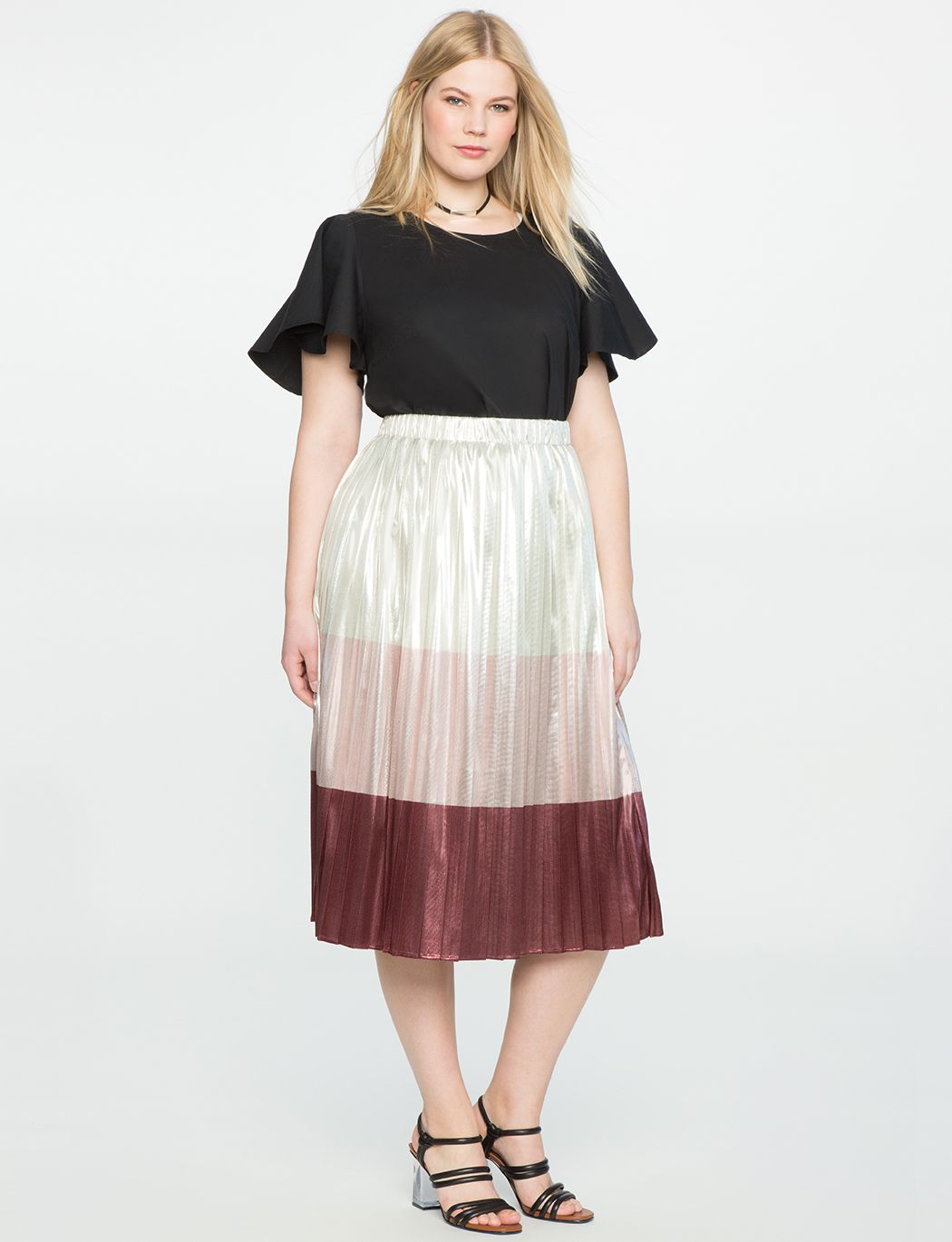 A model in a black tee and metallic skirt