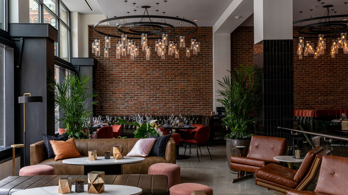 A wide shot of the front lounge area at leila looking towards a brick wall. The ceiling features a large circular chandelier and the lounge is filled with brown leather furniture and millennial pink furnishings.