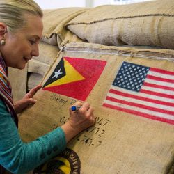 U.S. Secretary of State Hillary Rodham Clinton autographs a coffee bean sack while visiting the Timor Coffee Cooperative in Dili, East Timor Thursday, Sept. 6, 2012. U.S. Secretary of State Hillary Rodham Clinton is in East Timor to offer the small half-island nation support as it ends its reliance on international peacekeepers.