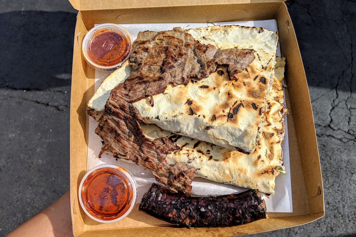 Tlayudas with tasajo and moronga from Poncho's in a paper box.