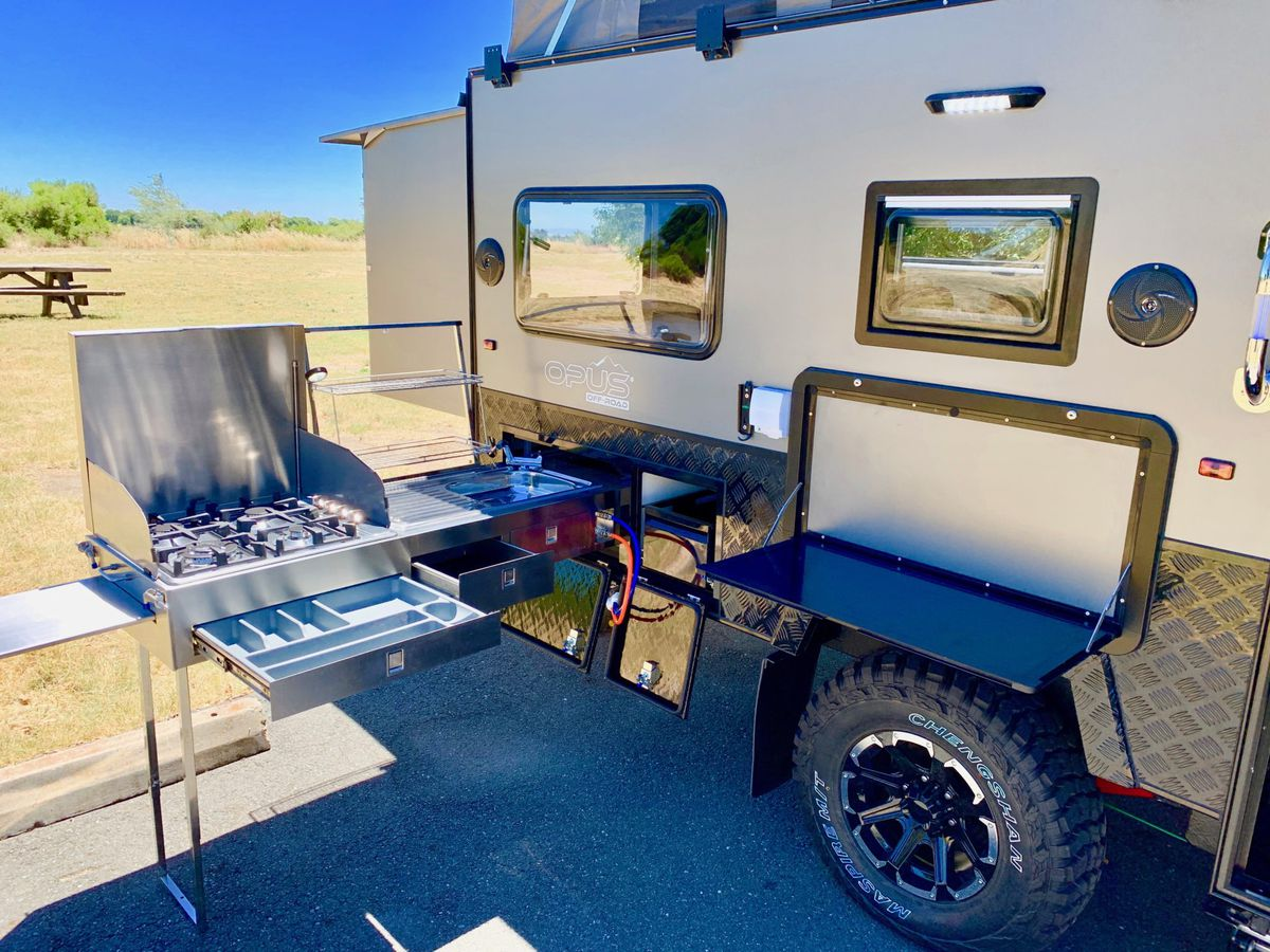 A stainless steel kitchen and stove top pulls out from the side of a gray and black trailer, and a flip-down table provides a space to prep food.